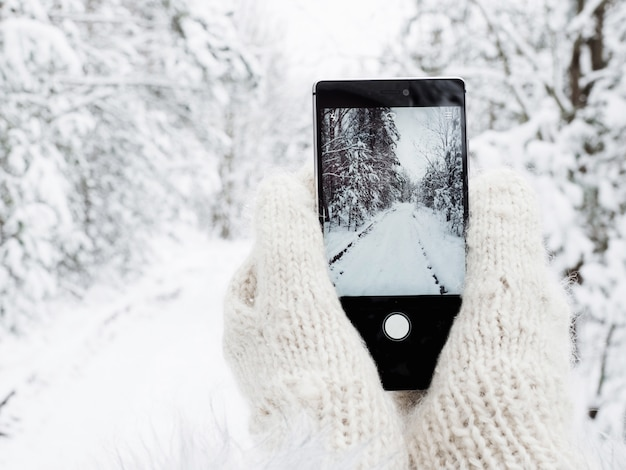 Girl is holding a mobile phone in woolen mittens