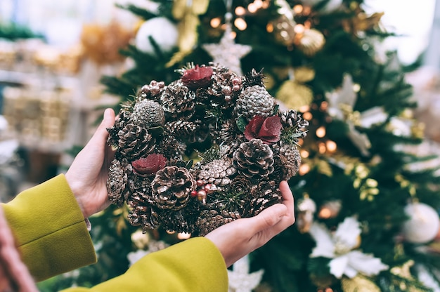 The girl is holding a new year's wreath in her hands. against the background of the christmas tree.
