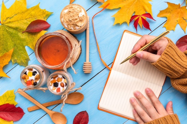 Girl is holding a notebook on the autumn table.