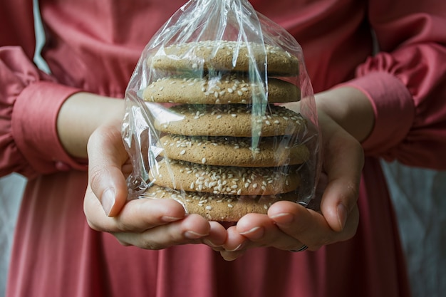 A girl is holding a package with oatmeal cookies.