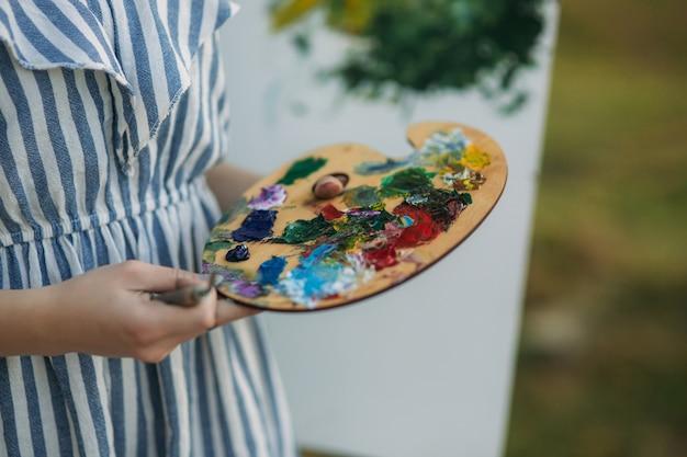 女の子は絵の具とヘラでパレットを保持しています