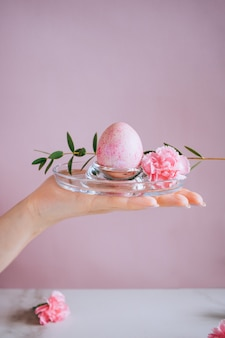 The girl is holding a pink easter egg on a stand, pink and marble background, minimalism, flowers