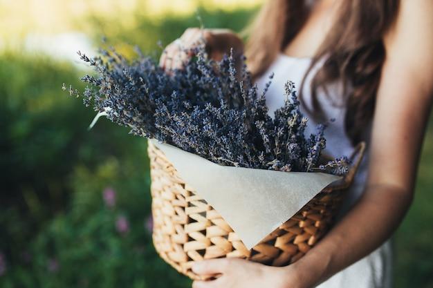 소녀는 나무 상자에 보라색 라벤더 꽃을 들고있다. 고품질 사진