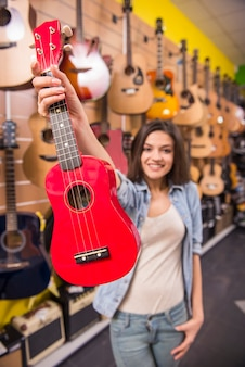 Girl is holding red ukulele in music shop.