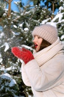 Девушка держит снег и дует на него. портрет молодой женщины в зимней шапке.