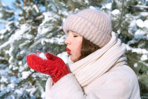 女の子は雪を持って吹いています