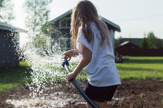 소녀가 채소밭에 호스를 집어넣고 있다
