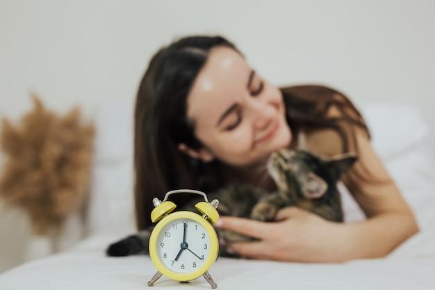 女の子は黄色の目覚まし時計で朝の焦点にベッドで彼のかわいい猫を抱いています