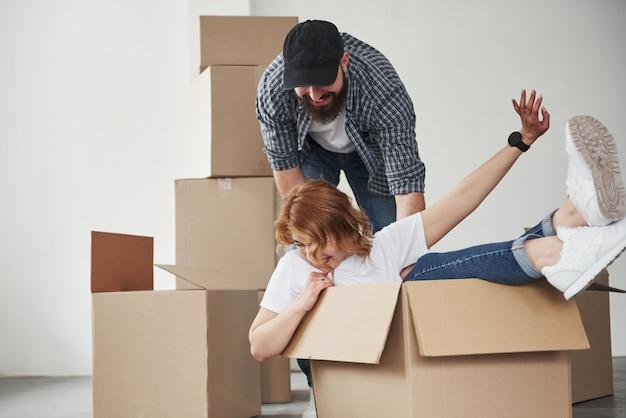 소녀는 상자 안에 있습니다. 그들의 새 집에서 함께 행복 한 커플입니다. 이사의 개념