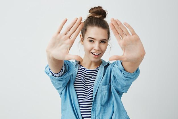 Девушка следит за тобой. портрет эмоциональной радостной кавказской женщины, тянущей руки к камере, делающей треугольник и просматривающей его с широкой улыбкой и знающей взгляд, стоящей над серой стеной