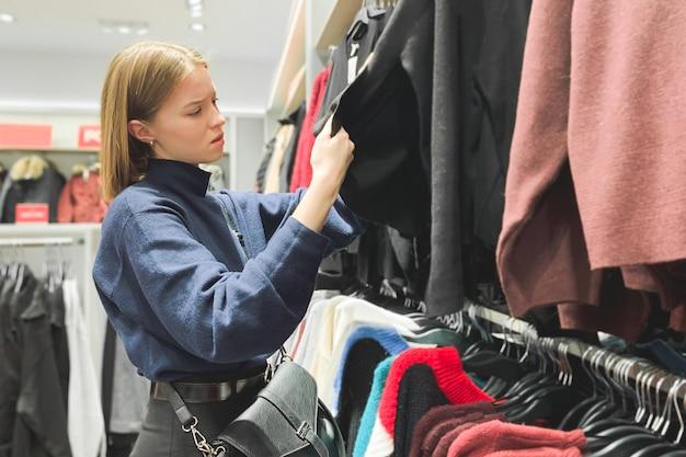 女の子は、ファッション店で服を見ています。