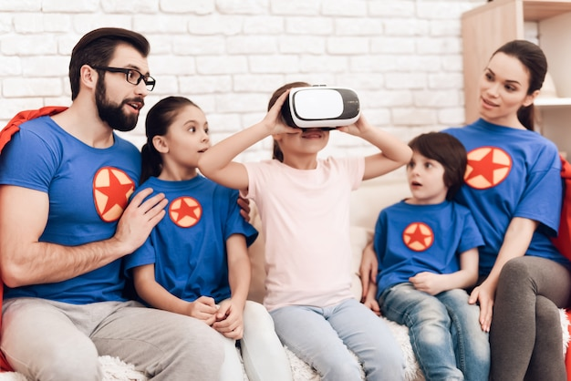 The girl is looking into virtual reality glasses.