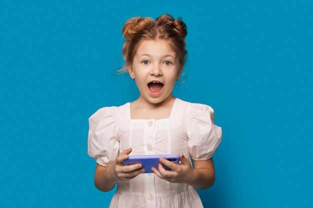 女の子は電話を持って口を開けてカメラに驚いて見ています