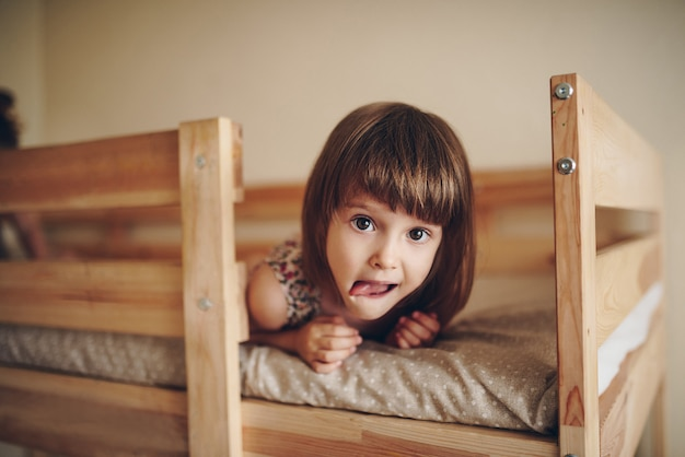 The girl is lying on the bed, looking at the camera and showing the tongue.