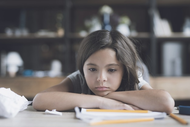 Girl is lying on the table, her head resting on crossed arms