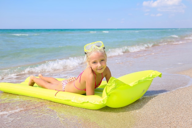 Girl is lying on yellow inflatable with googles and scuba diving on the beach