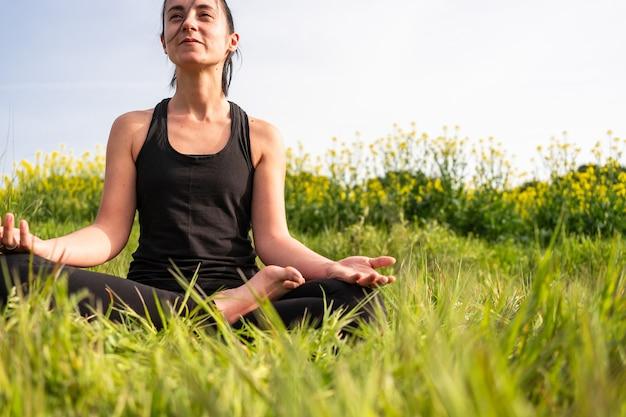 Девушка медитирует на природе летом
