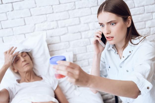 Girl is nursing elderly woman in bed at home