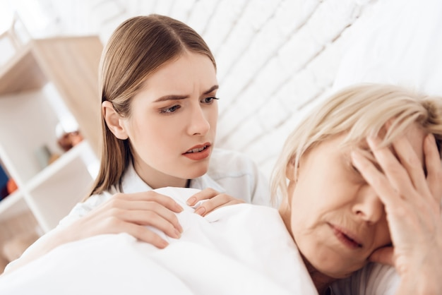 Girl is nursing elderly woman in bed at home.