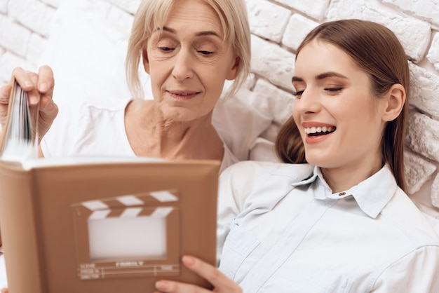 Girl is nursing elderly woman with photo album.