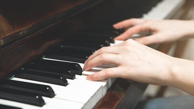 소녀는 피아노를 치고 있다. 음악 만들기. 격리 시간에 취미. 새로운 것을 배우다.