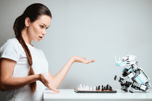 A girl is playing with a robot in chess.