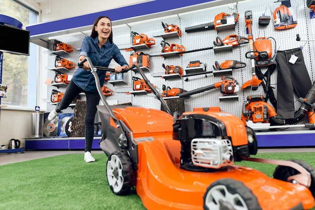 A girl is posing with a lawn mower in a tool store.