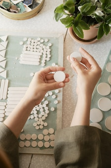 Girl is preparing to create ceramic jewelry from blanks
