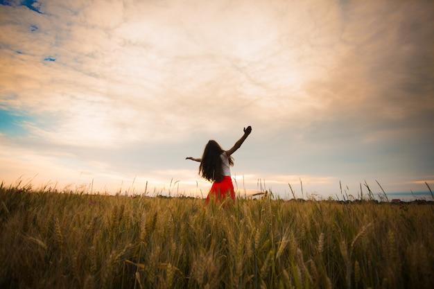 Девушка поднимает руки и наслаждается природой. мясистые колосья пшеницы на полях, яровой урожай