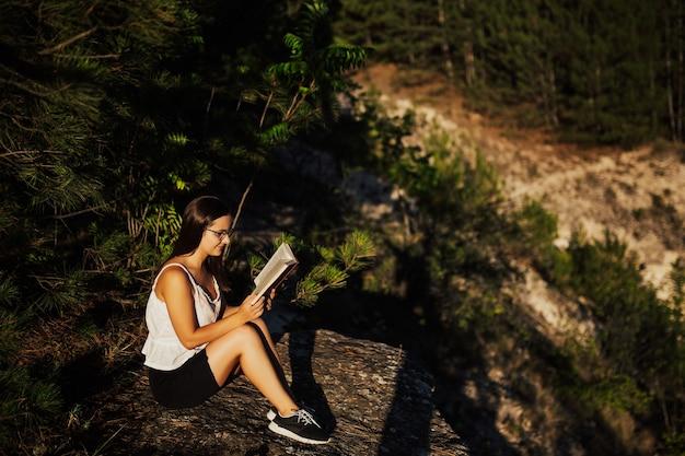 소녀는 책을 읽고 있으며 아름다운 자연 경관에 앉아 있습니다.