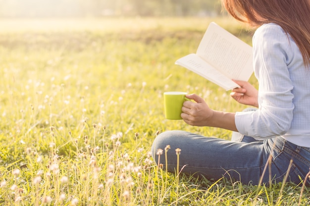 The girl is reading and taking a cup of coffee in the meadow with the morning sunshine.