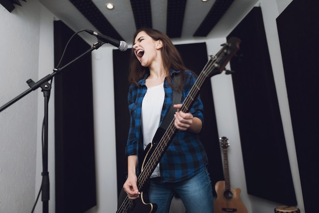 The girl is recording a song at a modern recording studio.