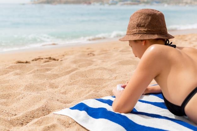 女の子はビーチの砂の上のタオルでリラックスし、手に日焼け止めを塗っています。
