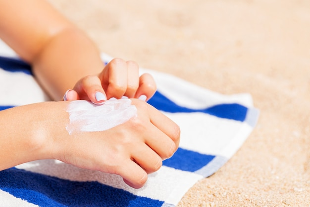 Girl is relaxing on the towel on the sand at the beach and applying sun lotion on her hand.