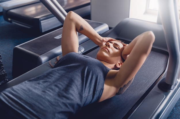 Girl is resting after doing exercise a treadmill