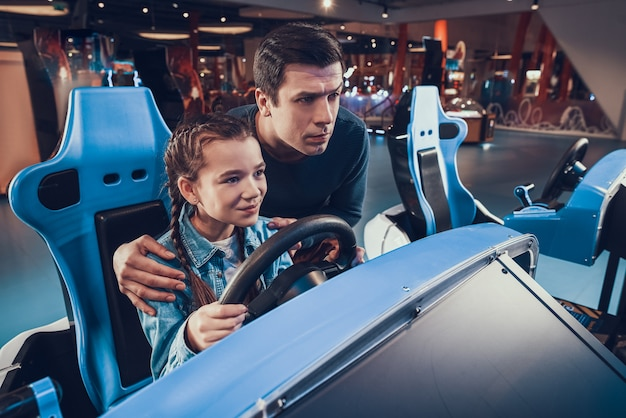 Girl is riding car in arcade. father is cheering and helping