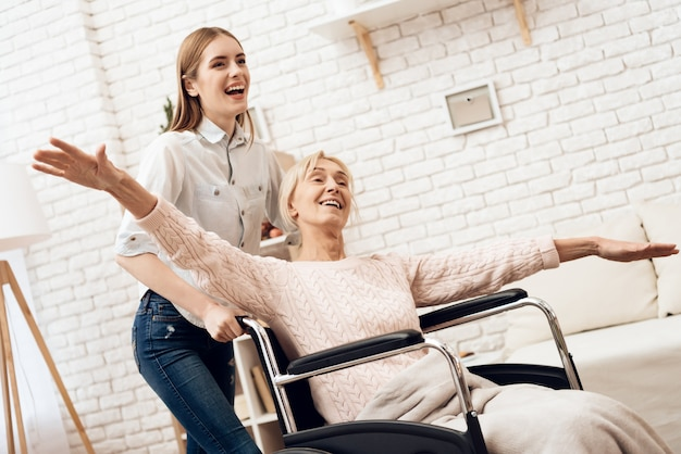 Girl is riding woman in wheelchair.
