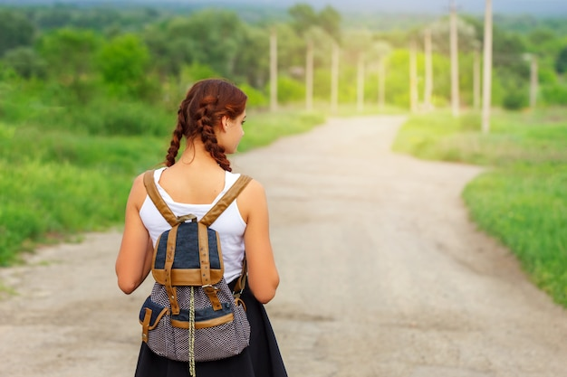 The girl is on the road with a backpack.