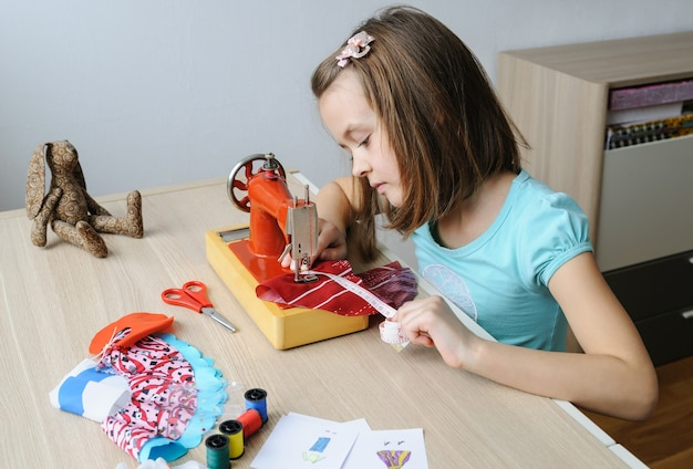 The girl is sewing a dress for a doll on a sewing machine. she using a measuring tape to measure the product.