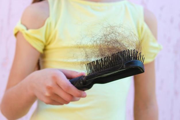 소녀는 빠진 머리카락의 양에 충격을 받습니다.