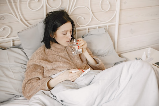 Girl is sick at home lying on the bed.