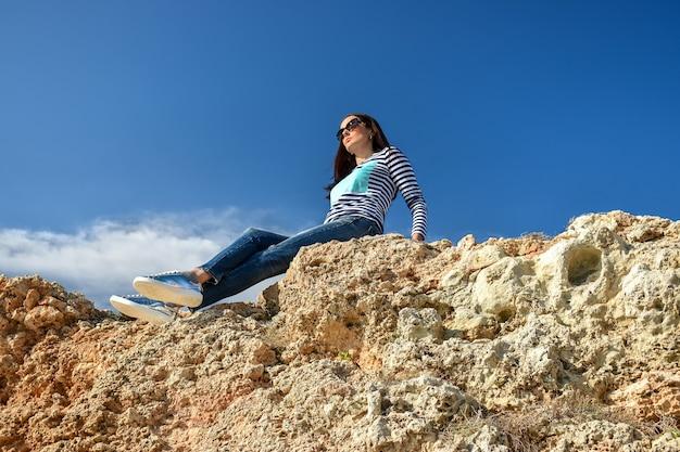Девушка сидит на скале и наслаждается видом.