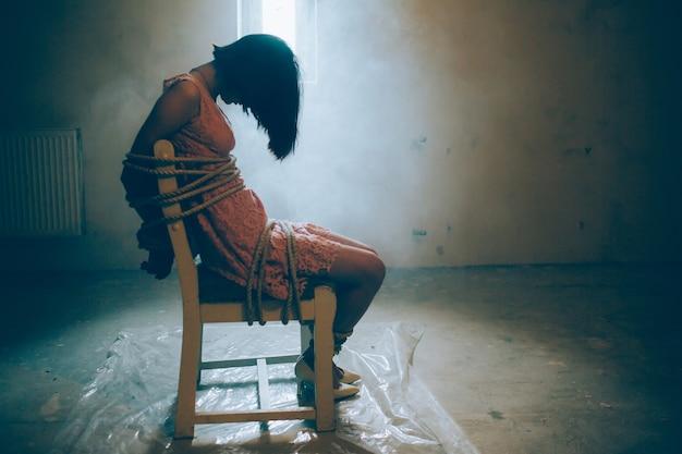 Девушка сидит одна. ее руки и ноги привязаны веревками к стулу.