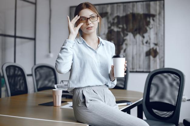 女の子がテーブルに座っています。カップを持っている女性。ブルネットがメガネを調整します。