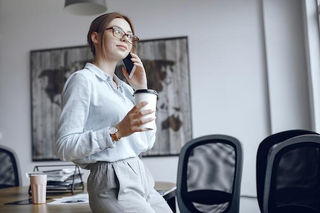 女の子がテーブルに座っています。電話で話している女性。コーヒーを飲むブルネット