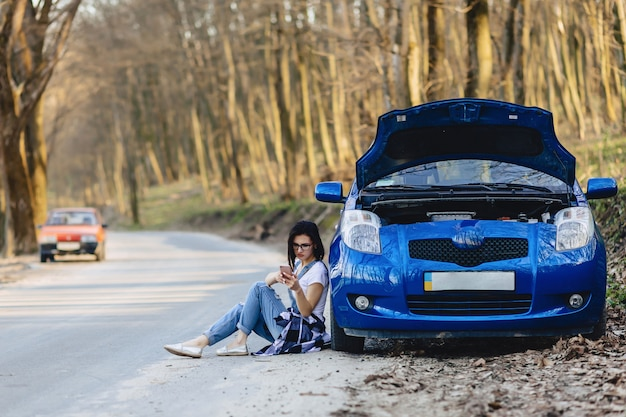 Girl is sitting next to broken car with an open hood and speaks by phone