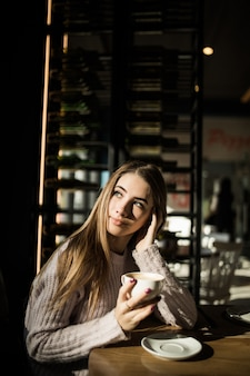 Girl is sitting in cafe with cup of coffee or tea. photo with shadows