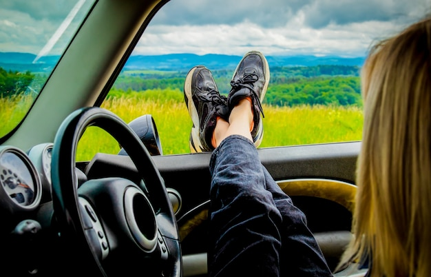 The girl is sitting in car with her feet out a window, mountains behind