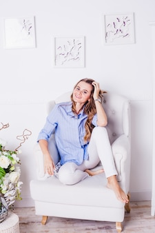 Girl is sitting on a chair in light clothes, beautiful flowers nearby, light interior