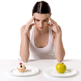 Girl is sitting and choosing between a cake and an apple. diet concept